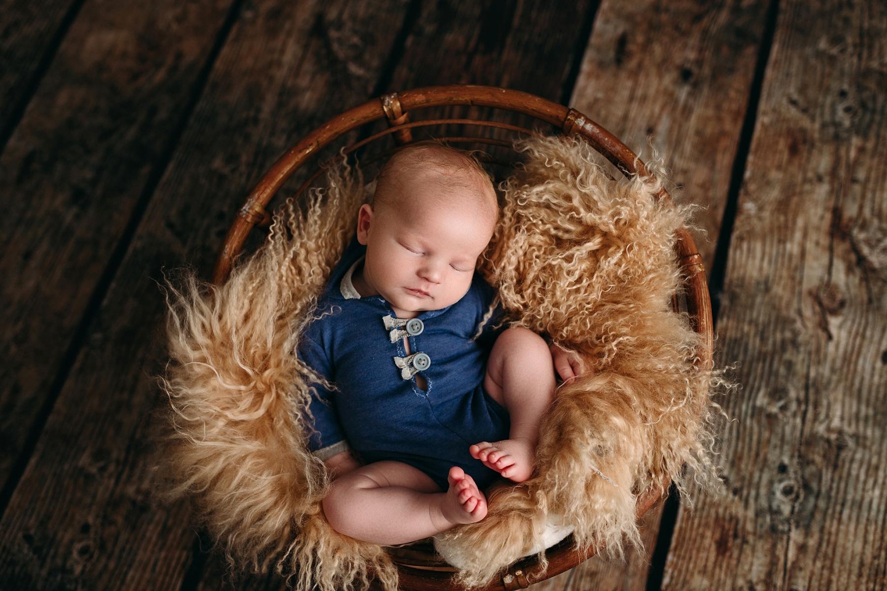 newborn boy posed on brown fur bowl in newborn photography studio