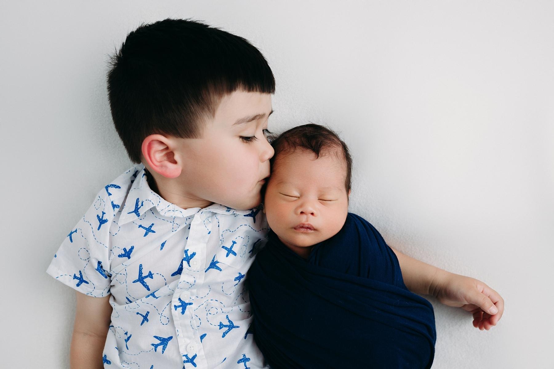 brother kissing newborn head