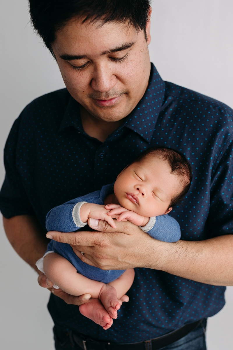 newborn head on hands in daddy's arms