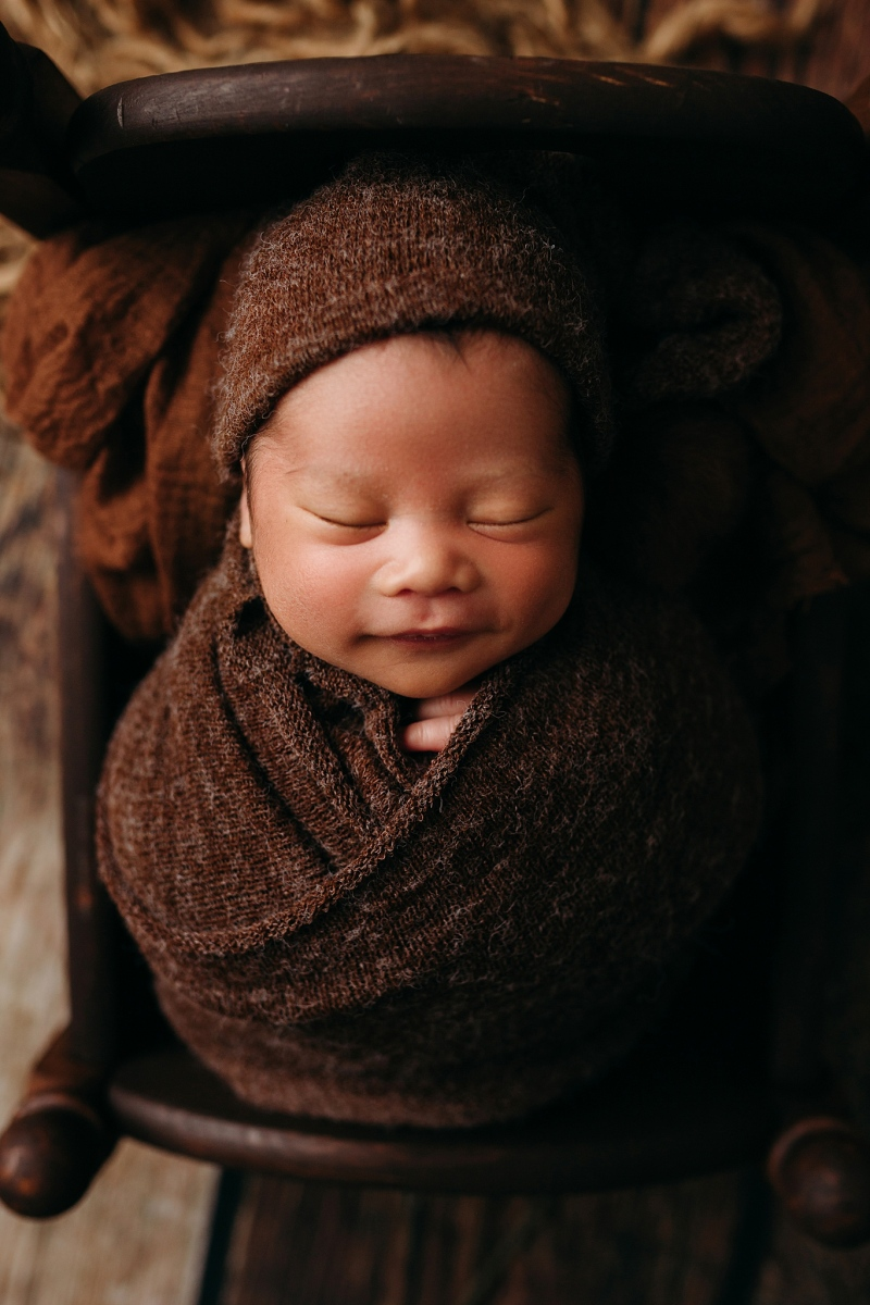 Asian newborn boy wrapped in brown wrap with hat newborn photos
