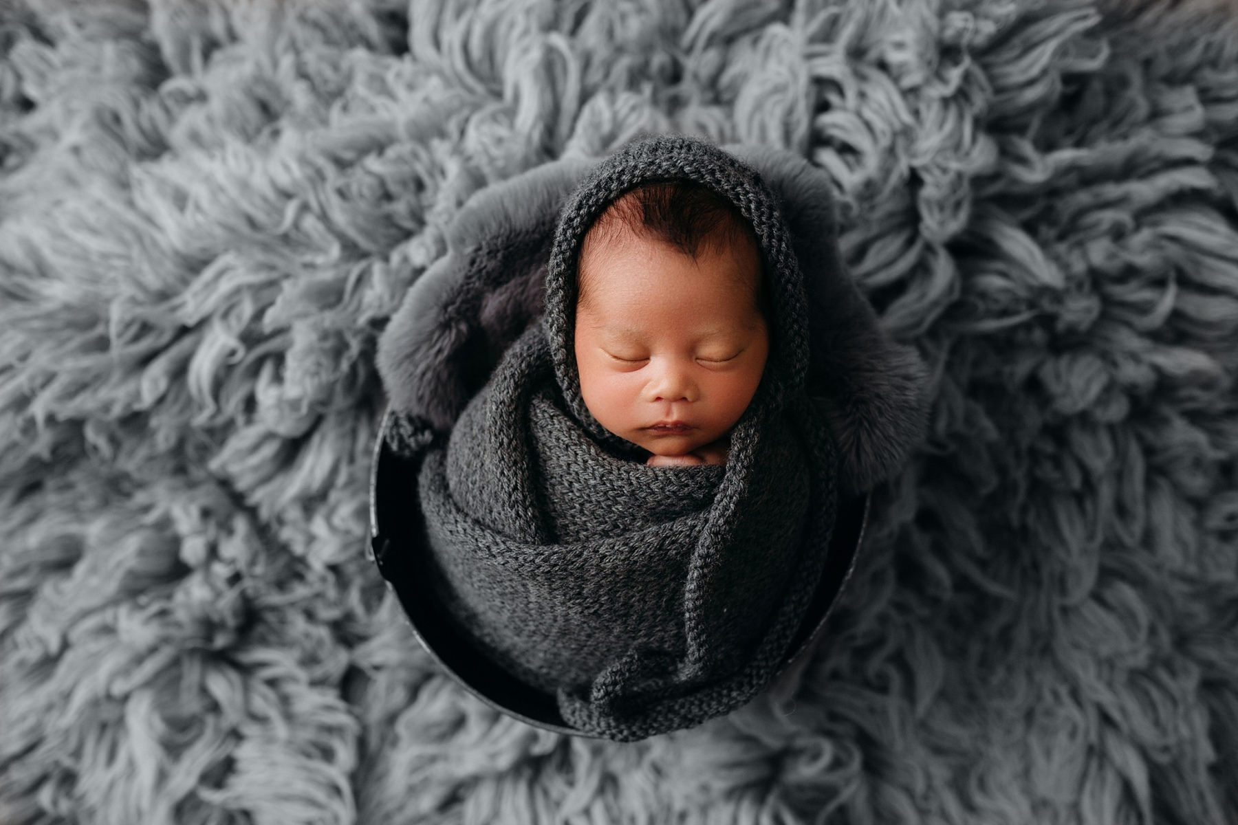 Newborn boy wrapped in gray wrap and bonnet in bucket on flokati