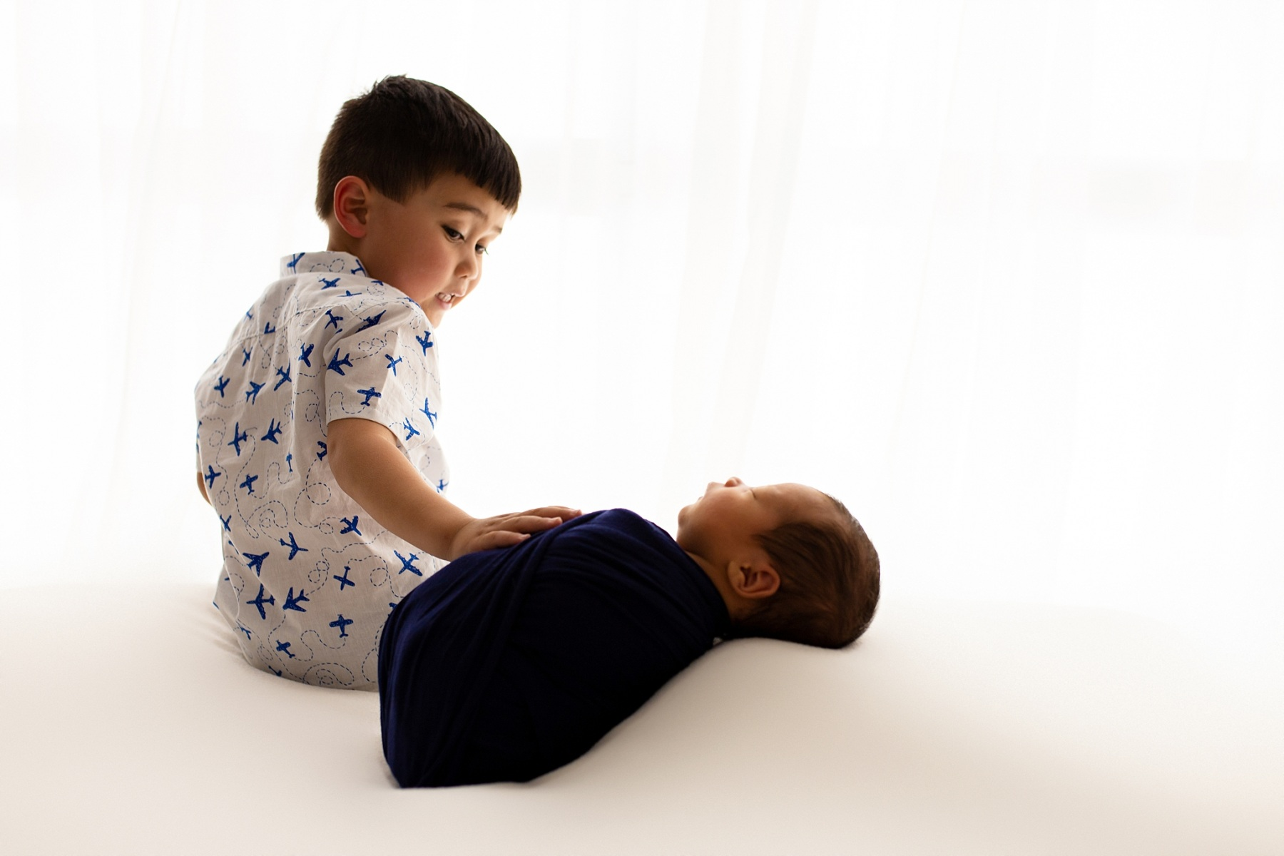 sibling brothers backlit posed newborn photography