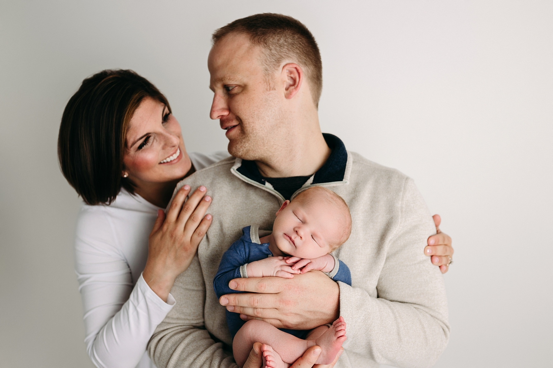 mommy daddy and me newborn photo session head on hands