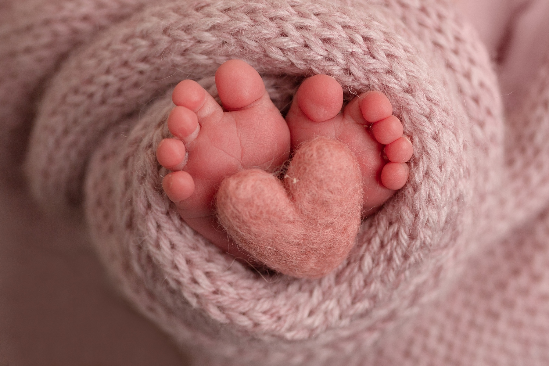 newborn baby toes with pink wrap and heart