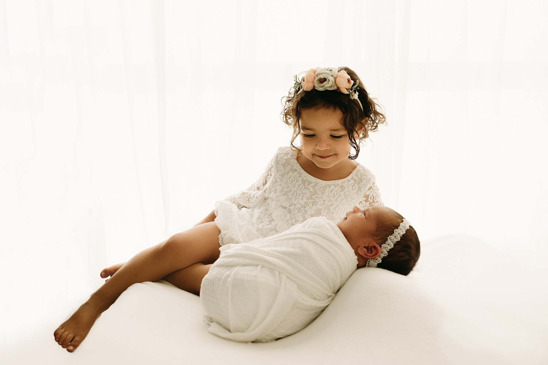 sibling newborn photo backlit on white