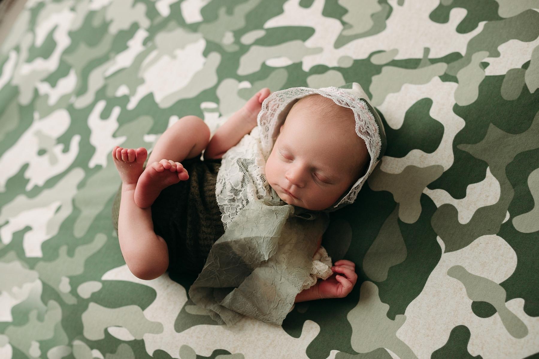 newborn baby girl in camo with bonnet