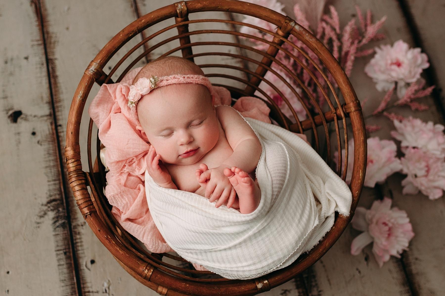 brown bowl holding newborn girl sleeping during milestone photo session