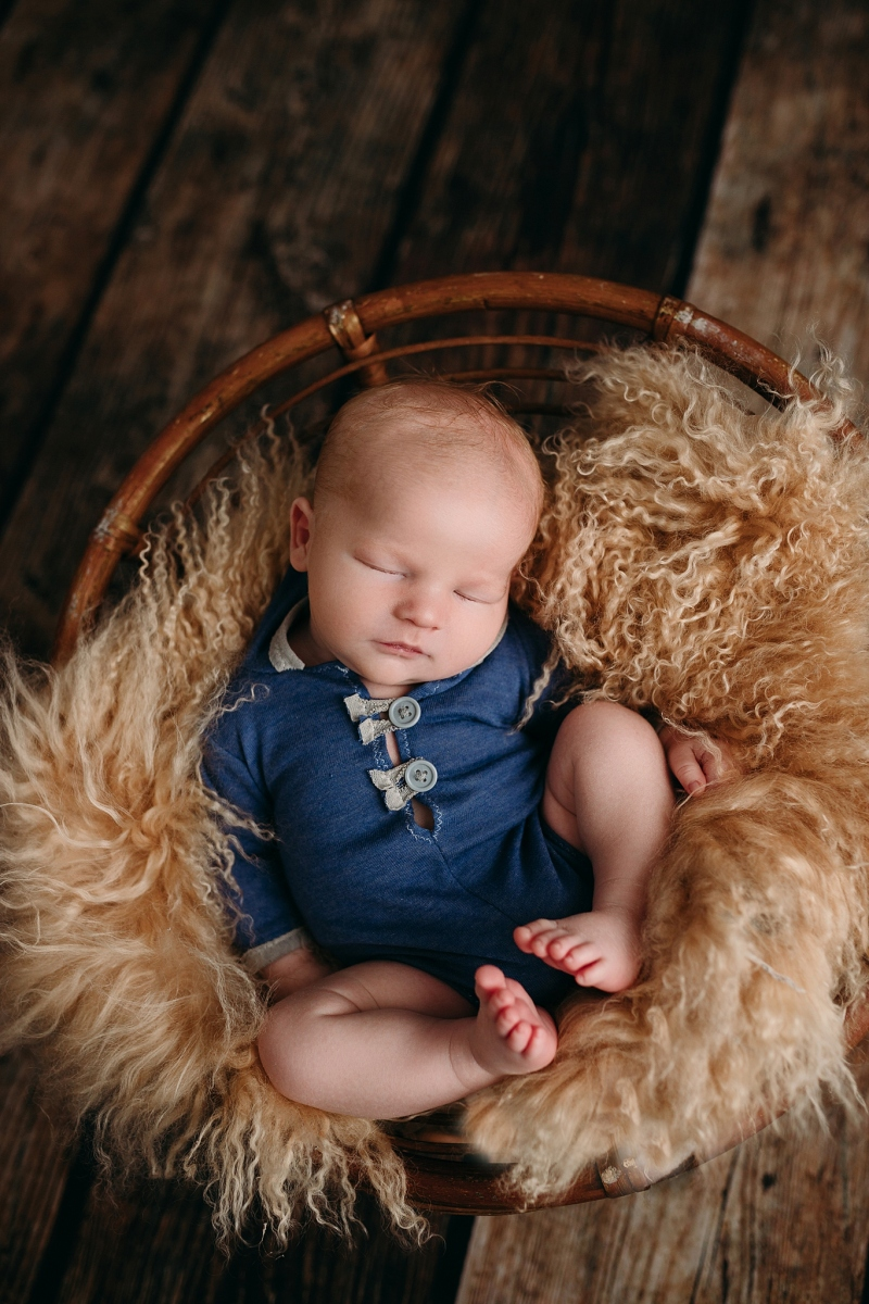 newborn boy sleeping in bowl blue outfit