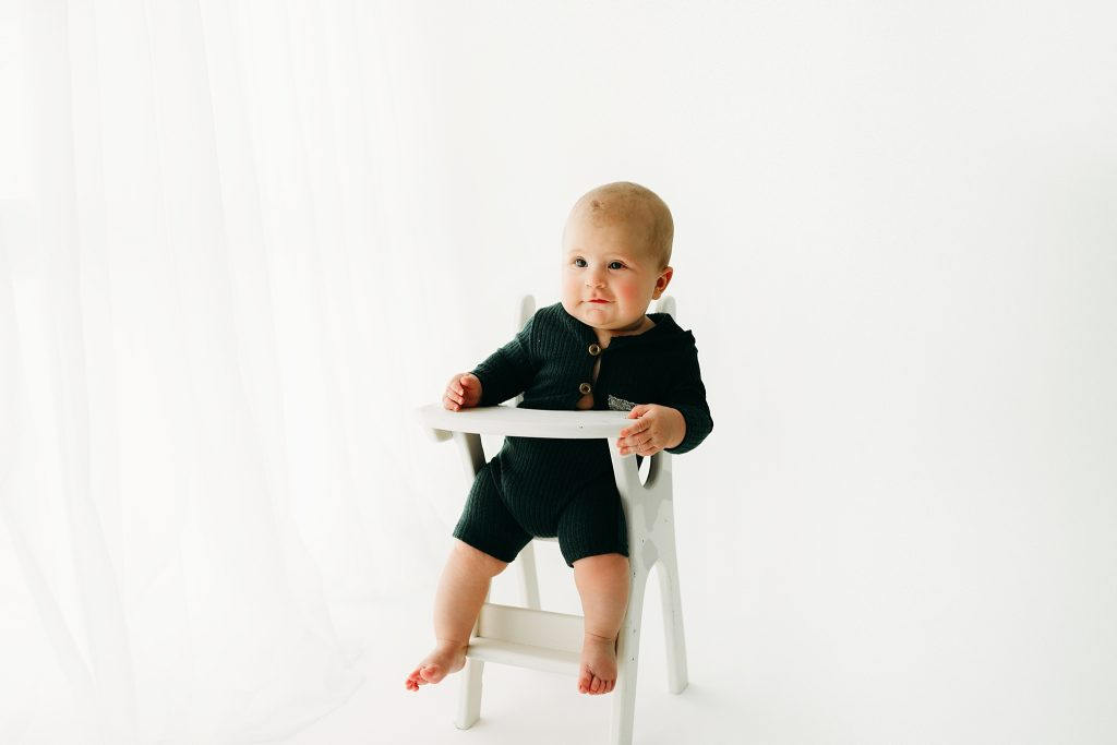 six month old baby boy sitting in highchair by window