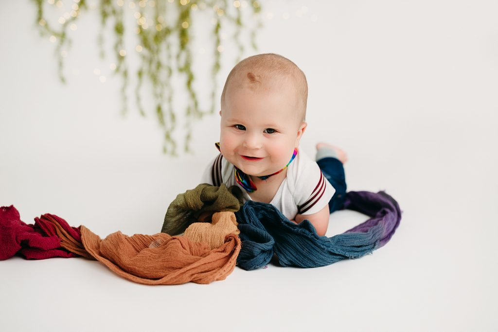 six month baby boy smiling at holly marie photography for pictures