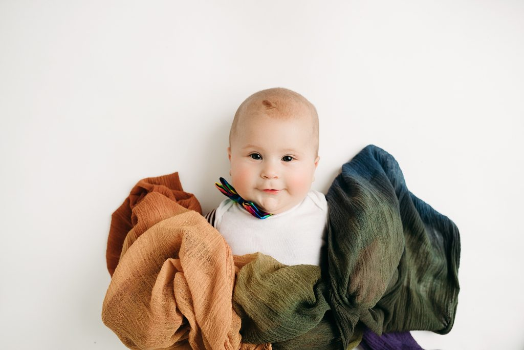 little boy with rainbow blanket posing for six month baby pictures