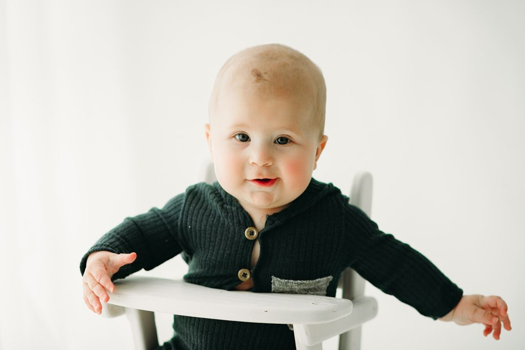 baby boy in gray romper in high chair for photo session