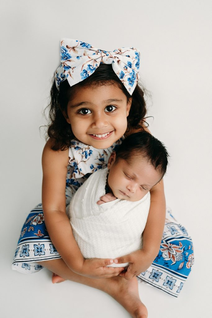 Sister holds newborn holly marie photography studio