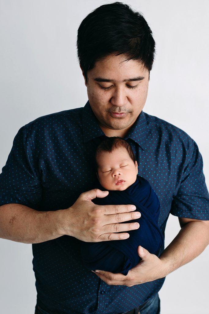 Dad holding wrapped baby newborn photos