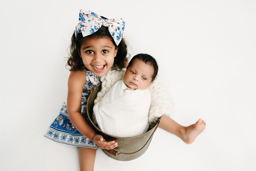 newborn in bucket with sister carmel photographer studio