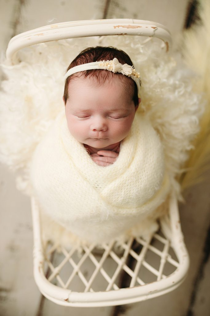 baby girl swaddled in yellow on bed