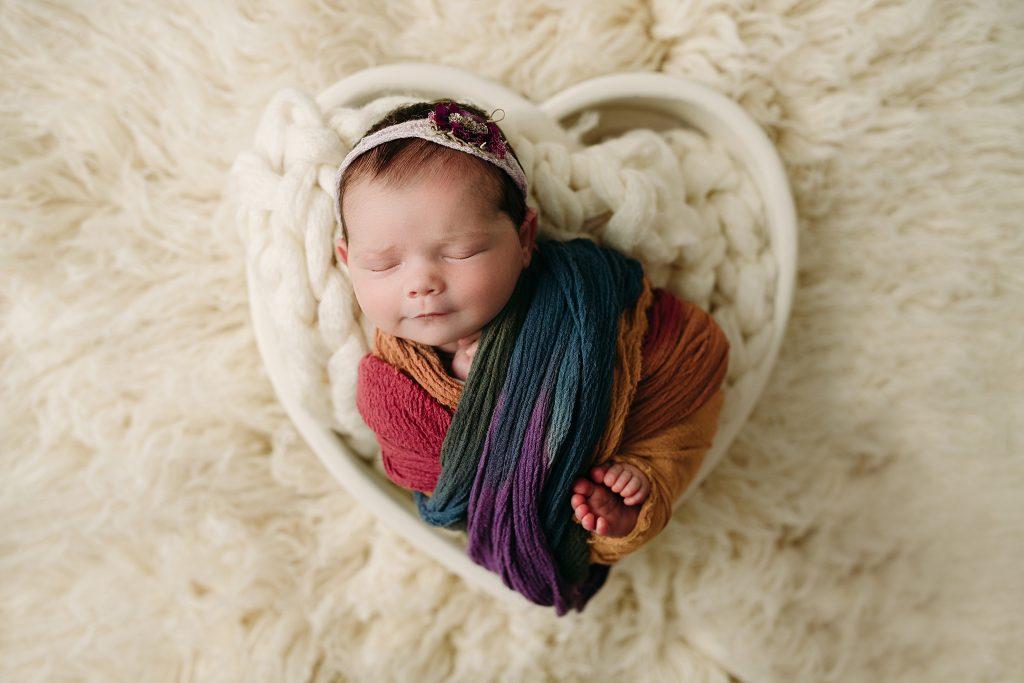 rainbow newborn girl in heart bowl
