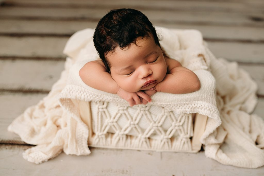 newborn boy in macrame box head on hands