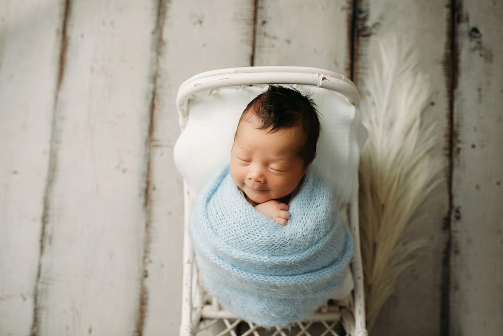 newborn smiling in crib at holly marie photography studio