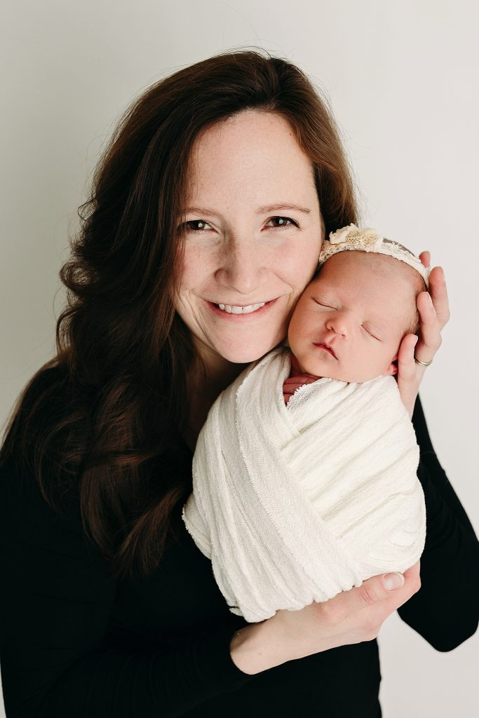 smiling new mom holding newborn wrapped at holly marie photography