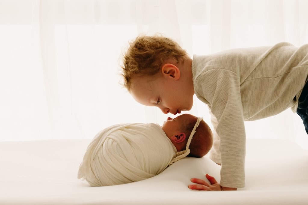 brother kisses sister baby photo session