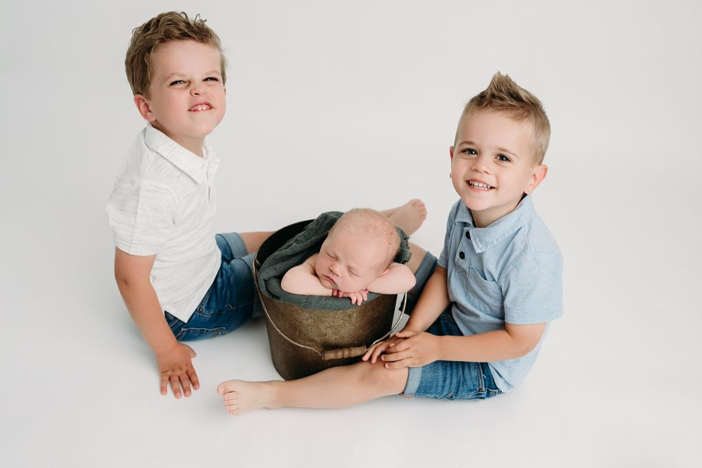 newborn in bucket with brothers