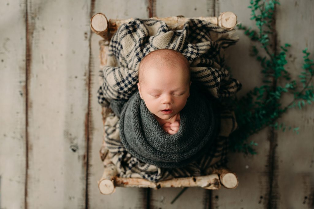 newborn boy swaddled in gray newborn session