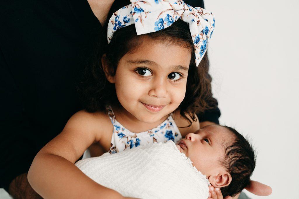 big sister holding swaddled newborn