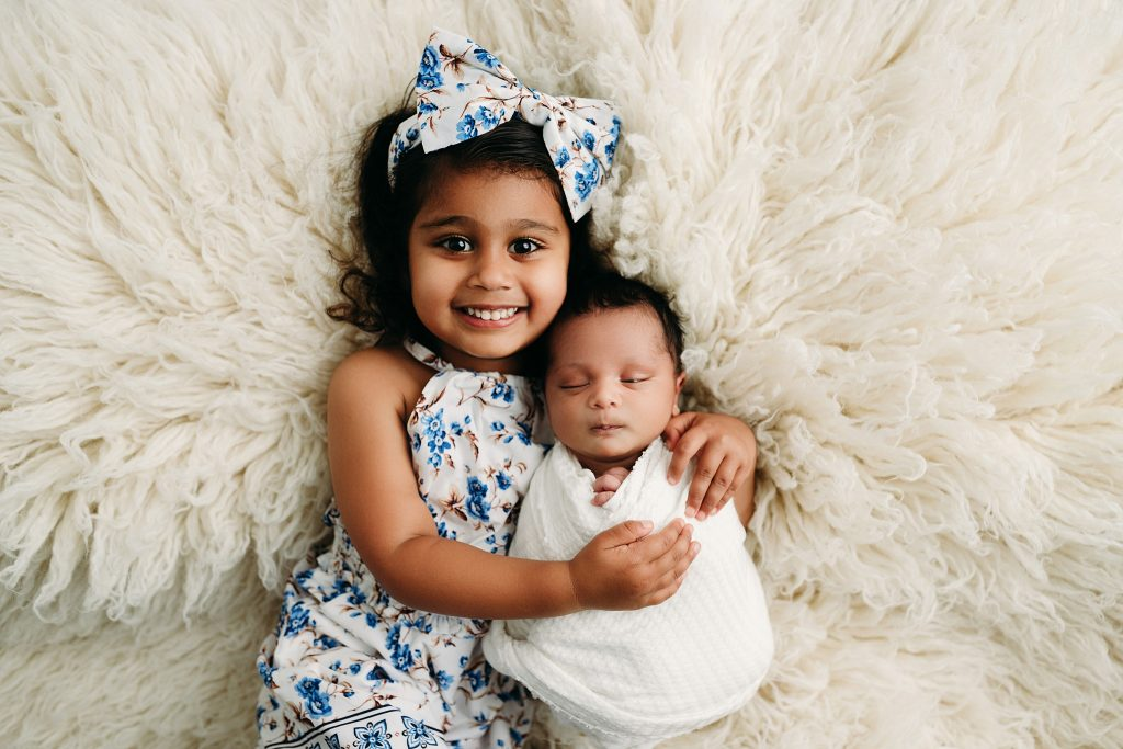 girl holding baby on fur for newborn baby pictures