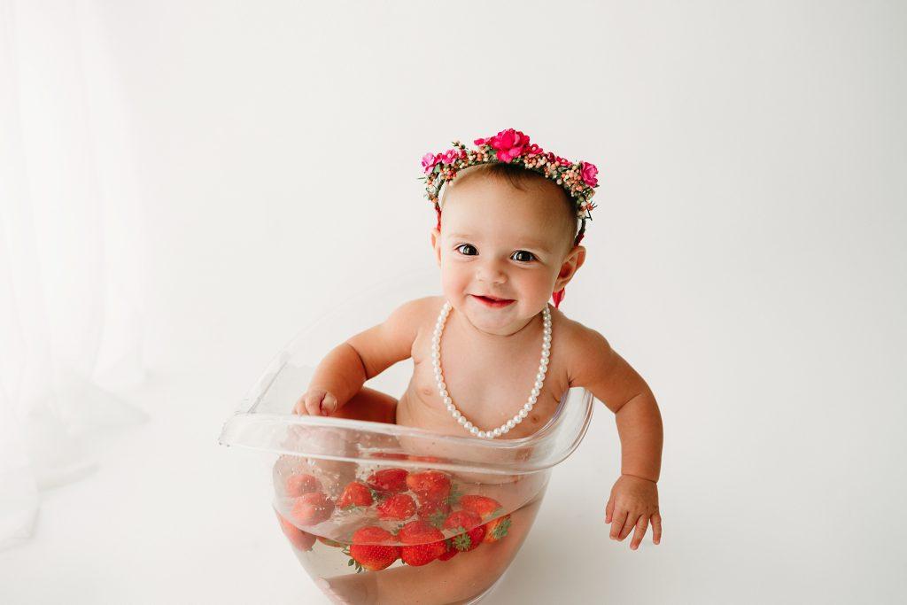 baby girl in strawberry bath for milestone photos